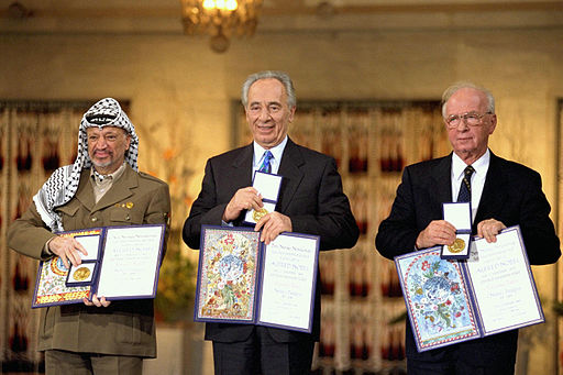The Nobel Peace Prize laureates for 1994 in Oslo. From left to right: PLO Chairman Yasser Arafat, Israeli Foreign Minister Shimon Peres, Israeli Prime Minister Yitzhak Rabin. Photo by Government Press Office (Israel) [CC BY-SA 3.0 (https://creativecommons.org/licenses/by-sa/3.0)], via Wikimedia Commons